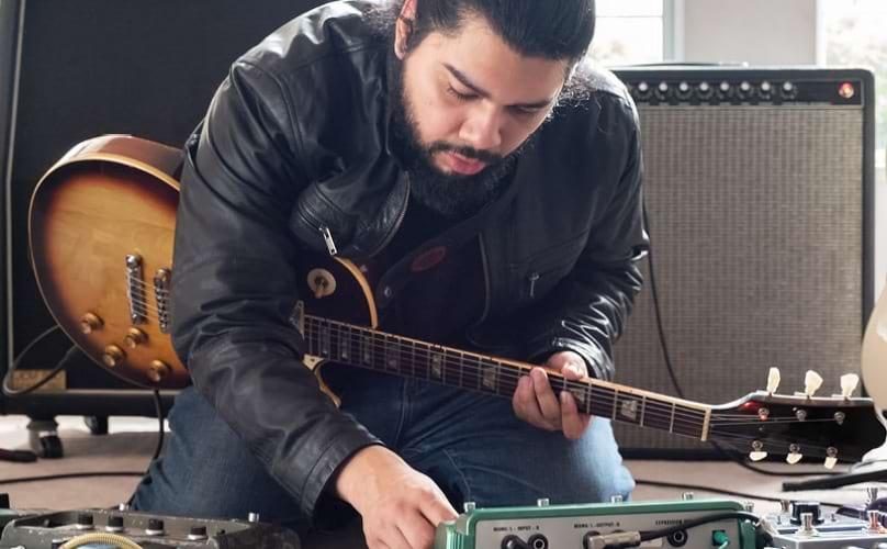 Man holding guitar recording music.