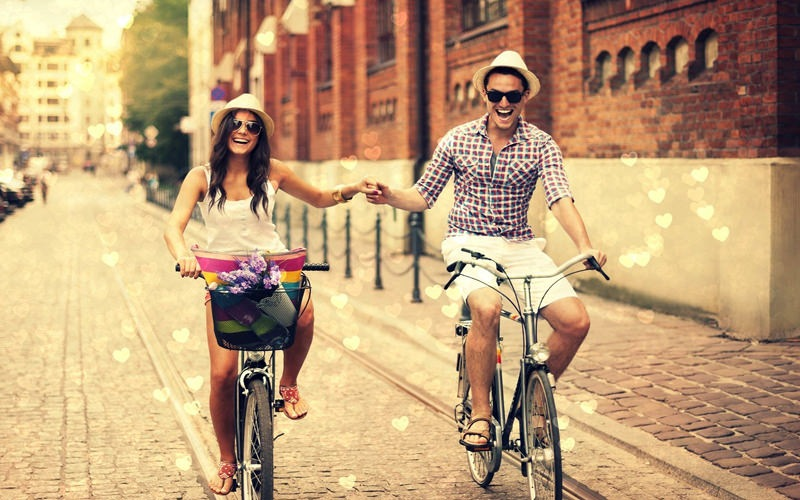 Man and woman holding hands while riding bike through the city.