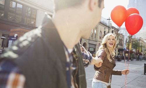 Man and woman walking through city with balloons.